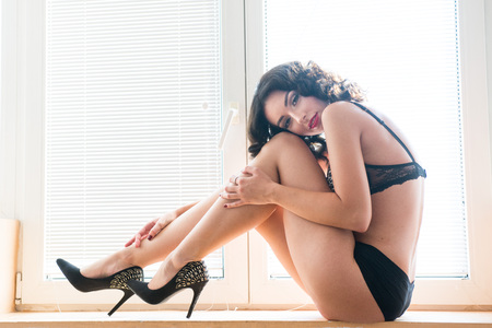 Beautiful young brunette woman with cheetah bra , black panties and stilettos laying down near the window, in house
