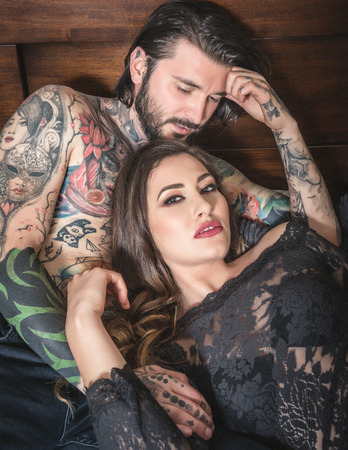 Young tattooed man interacting with a sensual woman dressed in lace, in bed, in doors Stock Photo