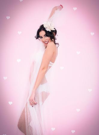Caucasian brunette in white lingerie smiling on pink heart background. Valentines Day boudoir concept.