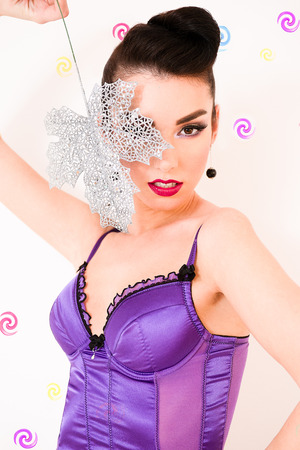 Caucasian brunette in purple corset looking sexy through a silver leaf on white candy background
