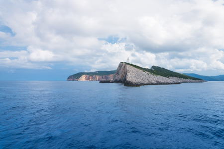 Blue ocean landscape with a green island with lighthouse in the background, in Lefkada, Greece Foto de archivo - 109996573