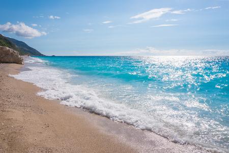 Blue ocean shore with golden sands and rocks, in Lefkada, Greece Foto de archivo - 109996575