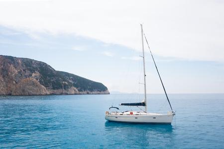 White boat sailing on the blue sea coast in Lefkada, Greece Foto de archivo - 109996631