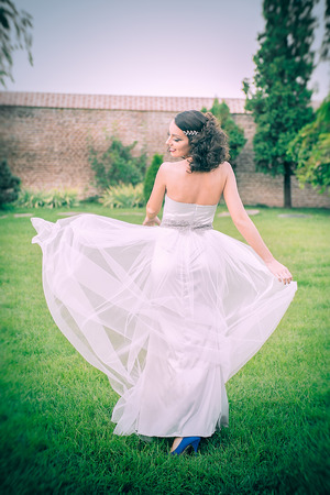 Sexy curly hair bride, playing with her tulle dress and looking over the shoulder, in the garden lawn