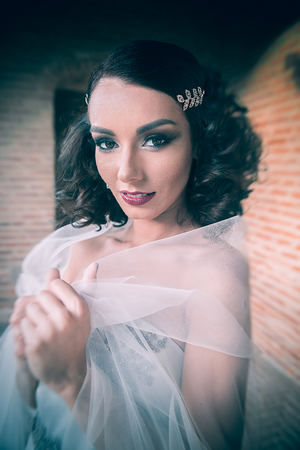 Sexy curly hair bride portrait, looking straight and covering herself with white tulle, on the palace corridor