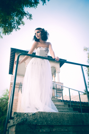 Sexy curly hair bride, looking aside, leaning against a metal bar, on the palace stairs. Bottom-up view