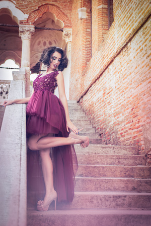 Sensual caucasian curly hair woman looking over the shoulder and fixing her high heel on the palace stairs, in a redwine tulle dress Stock Photo