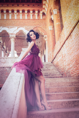 Sexy curly hair woman looking over the shoulder and showing her legs on the palace stairs, in a redwine tulle cocktail dress