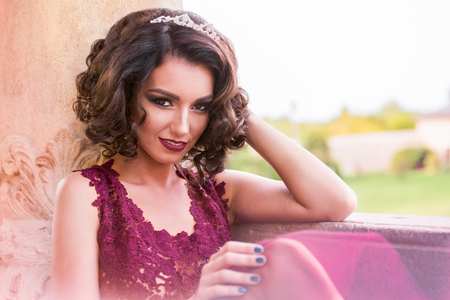 Sexy curly hair woman portait looking straight and smiling, in a redwine tulle dress