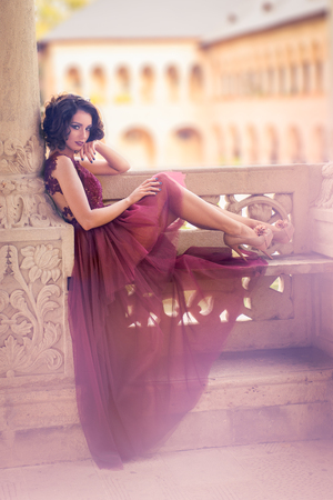 Sexy curly hair woman sitting on a stone bench and looking from one side, in a redwine tulle dress, at Mogosoaia Palace
