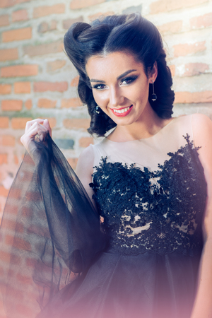 Sexy dark hair woman portrait smiling and playing with her black tulle dress against a brick wall