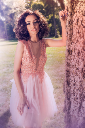 Curly Caucasian woman in party dress in the garden, looking straight and leaning against a tree