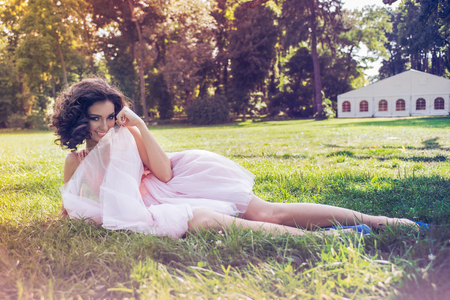Curly Caucasian woman lying down in the garden and looking playfully from behind of her party pink dress
