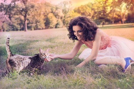 Curly Caucasian woman dressed in a party tulle dress, sitting down and playing with a cat in the garden Stock Photo