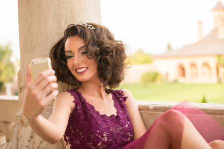 Sexy Caucasian model with curly hair and cocktail purple dress taking a selfie with the phone and smiling