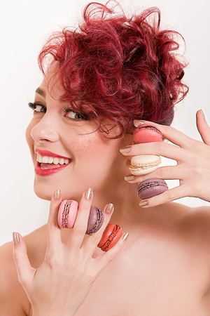 Beautiful sexy redhead woman smiling and having six colored macarons between her fingers, having red glitter on the cheeks and bare sholders, on white background Foto de archivo - 109893572