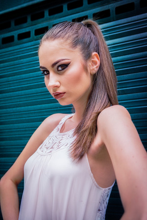 Beautiful Caucasian girl with ponytail and white dress, looking fashion, next to a turqoise door, on the street in the city, during daytime