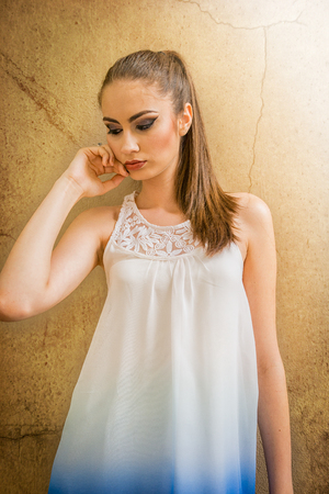 Beautiful Caucasian girl with ponytail and white dress, touching her face, on golden background, during daytime Foto de archivo - 110088286