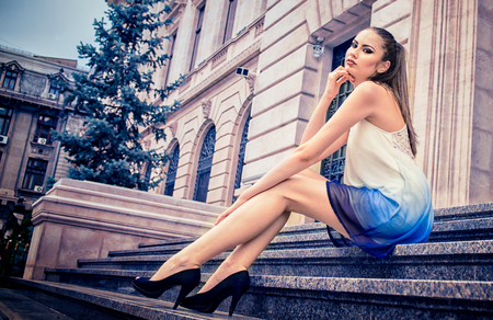Beautiful Caucasian girl with ponytail,  white dress and high heels, sitting down on the stairs of a building, outdoor, in the city, during daytime Foto de archivo - 110088289