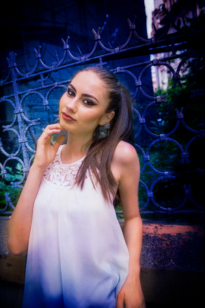 Beautiful Caucasian girl with ponytail and white dress, touching her face and smiling, next to an ornamental fence, on the street, in the city, during daytime