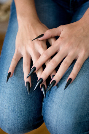 Detail shot of woman stiletto black and sharp nails Foto de archivo - 118726600