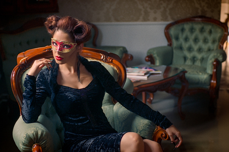Sexy Caucasian model with carnival red mask standing on a baroque couch, indoors, with her black stiletto nails, sculpting make-up and cocktail dress with big cleveage. Maleficent lookalike retro concept Foto de archivo - 118726609