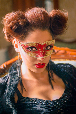 Sexy Caucasian model with carnival red mask standing on a couch, indoors and looking straight, with sculpting make-up and cocktail dress with big cleveage. Maleficent lookalike retro concept