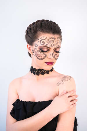 Sexy female model with braided hair, big eyes and decorative tattoo on her face, touching her shoulder and looking down, on white background Banque d'images