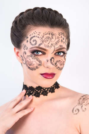 Sexy female model with braided hair, big eyes and decorative tattoo on her face, touching her neck and looking down, on white background