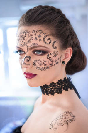 Sexy female model with braided hair, big blue eyes and decorative tattoo on her face, looking away from profile, on blue background