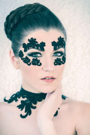 Young female model with braided blonde hair, big green eyes and decorative black lace on her face, touching her neck, on white lace background
