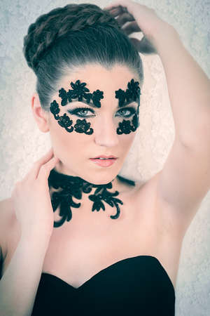 Young female model with braided blonde hair, big green eyes and decorative black lace on her face, touching her neck and hair, on white lace background