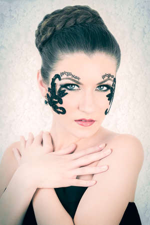 Young female model with braided blonde hair, big green eyes and decorative black lace and black tattoo on her face, touching her chest, on white lace background Banque d'images