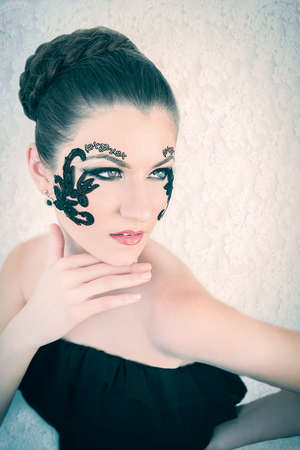 Young female model with braided blonde hair, big green eyes and decorative black lace on her face, touching her chin, on white lace background