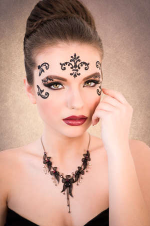 Gorgeous female model with blonde hair and big eyes and decorative tattoo on her face, pulling her necklace, on golden background