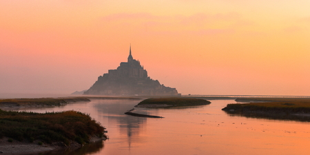 A sunrise in fog on September gone in red in the estuary of the River Couesnon. High tide water Creates a path That leads to the abbey of Mont Saint Michel Stock Photo