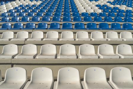 gradas estadio: Rows of empty bleachers positioned in a semicircular pattern. Stadium seats before an event. Foto de archivo