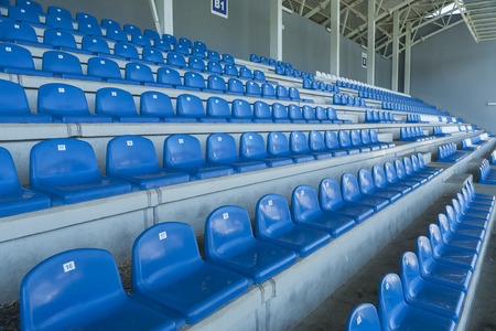 positioned: Rows of empty bleachers positioned in a semicircular pattern. Stadium seats before an event. Stock Photo