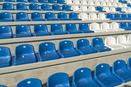 semicircular: Rows of empty bleachers positioned in a semicircular pattern. Stadium seats before an event. Stock Photo