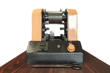 small group of objects: Printing at high speed on offset machine. Label, Rolled Up, Printing Out, Group of Objects, Merchandise. Old small printing machine in company office. Stock Photo