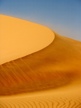 Wind blowing on a dune in the Rub al Khali or Empty Quarter. Straddling Oman, Saudi Arabia, the UAE and Yemen, this is the largest sand desert in the world. photo