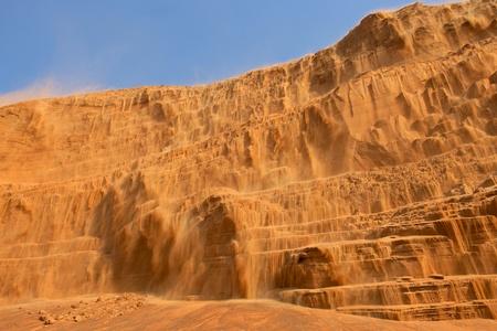 gcc: A waterfall of sand in the desert near Dubai in the United Arab Emirates. Stock Photo