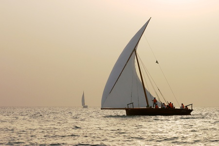 Traditional racing dhows dhows at sunset in the Arabian Gulf off Dubai. photo