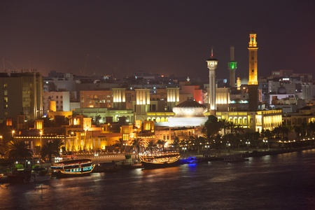 A night-time view of dhow restaurants on Dubai Creek, with the historic district of Bastakiya in the background.
