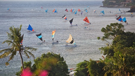 Fishermen in traditional sailing jukungs (outrigger canoes) returning with their catch to Ahmed's 'Japanese Wreck' beach in Bali, Indonesia. Stock Photo - 12343713