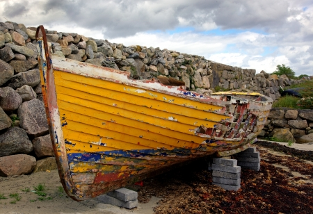 rotting: An old fishing boat rotting in the small harbour at Barna, near Galway, Ireland  Stock Photo