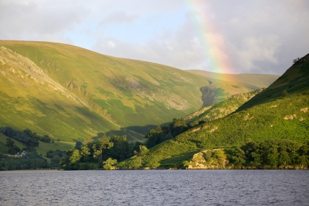 enhances: A rainbow enhances a scenic backdrop to Ullswater in Englands Lake District. Stock Photo