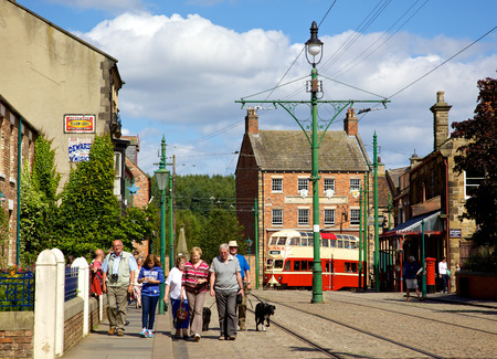 northeast: BEAMISH, UK - NOVEMBER 27, 2012: Tourists, tramlines and an old tram in the high street of the Edwardian town that forms part of Beamish Museum in County Durham, England. Beamish is a world-famous open-air museum that tells the story of life in North-East