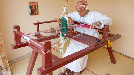 headcloth: MUSCAT, OMAN - FEBRUARY 1, 2008  An Omani weaver, wearing a traditional muzzar  headcloth , at work in Muscat, in the Sultanate of Oman