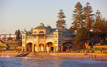 Swimmers relaxing and bathing at sunset in front of the iconic old pavillion at Cottesloe Beach in Perth, Western Australia